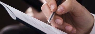 Человек пишет ручкой в тетради